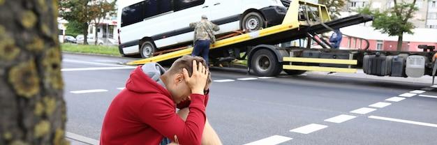Mann sitzt am straßenrand und hält seinen kopf mit den händen neben dem zerstörten auto nach einem autounfall. verkehrsverletzungskonzept