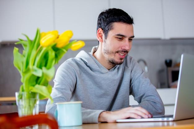 Mann sitzt am tisch mit kaffee und laptop