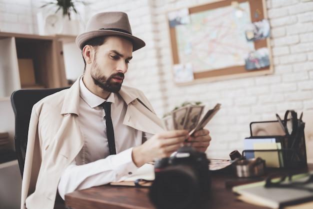 Mann sitzt am tisch und zählt geld.