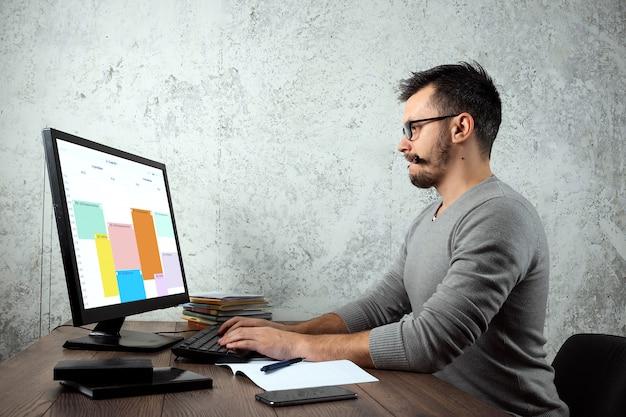 Mann sitzt an einem tisch im büro und arbeitet an einem computer.