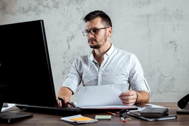 Mann sitzt an einem tisch im büro und arbeitet an wichtigen papieren. das konzept der büroarbeit. kopieren sie platz.