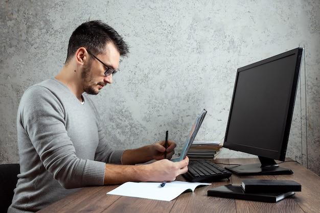 Mann sitzt an einem tisch im büro und arbeitet an wichtigen papieren.