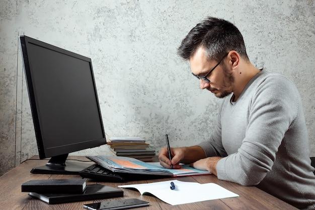 Mann sitzt an einem tisch im büro