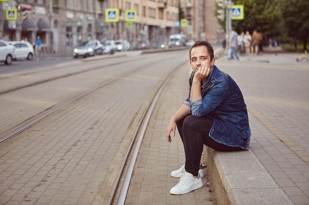 Mann sitzt auf bürgersteig nahe eisenbahn.