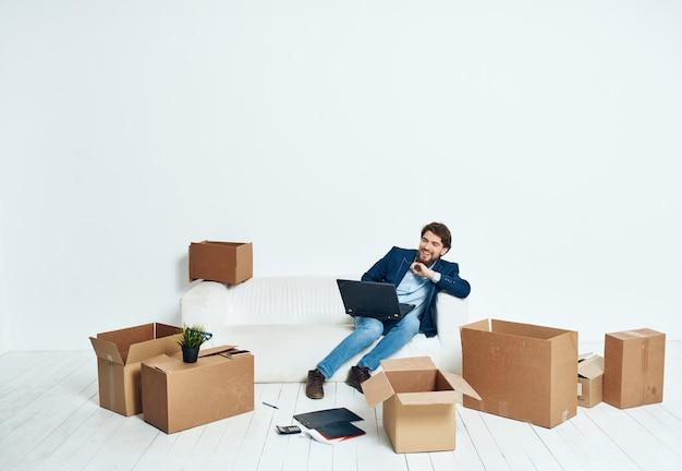 Mann sitzt auf couchboxen mit dingen neuer arbeitsplatzarbeitsfachmann