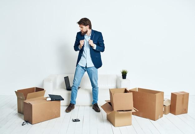 Mann sitzt auf dem boden mit kartons mit sachen, die arbeit bewegen