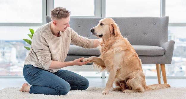 Mann sitzt auf dem boden und hält die pfote des golden retriever-hundes in der hand. besitzerin mit süßem hündchen im hellen sonnigen zimmer