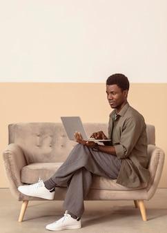 Mann sitzt auf dem sofa und arbeitet