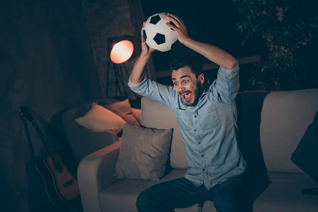 Mann sitzt auf dem sofa und sieht tv-sportshow