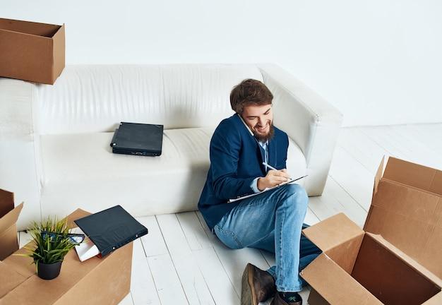 Mann sitzt auf den bodentanks mit sachen büro neuer arbeitsplatz lebensstil