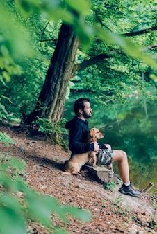 Mann sitzt auf der bank mit dem hund am see