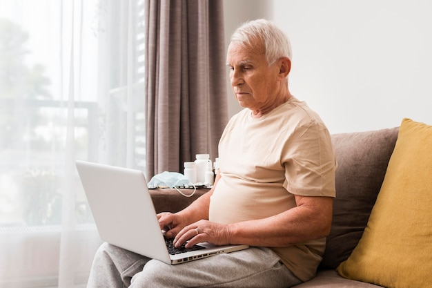 Mann sitzt auf der couch mit laptop