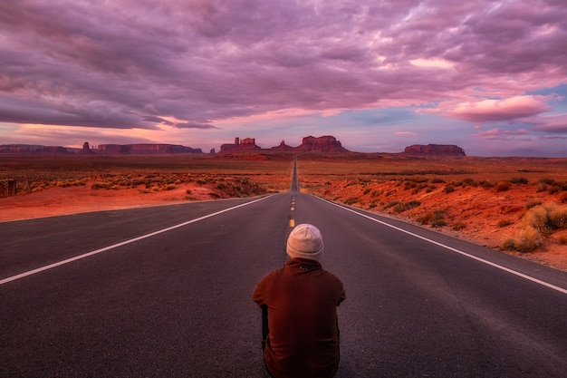 Mann sitzt auf der straße und bewundert erstaunlichen sonnenaufgang mit rosa, gold und magentafarben nahe monument valley, arizona, usa.