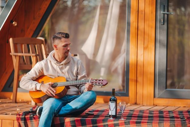 Mann sitzt auf der terrasse seines hauses im herbst und spielt gitarre