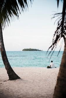 Mann sitzt auf der tropischen insel