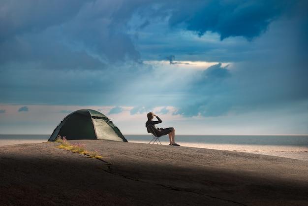 Mann sitzt auf einem campingstuhl auf einer steininsel. gewitter nähert sich.