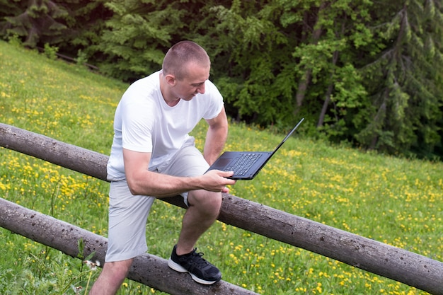 Mann sitzt auf einem holzzaun und arbeitet mit einem laptop in der nähe des feldes und des nadelwaldes