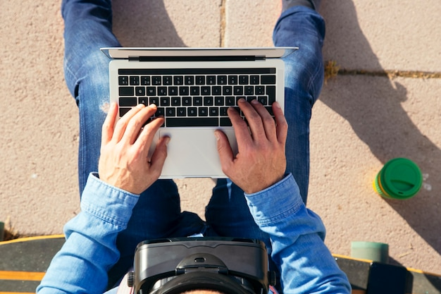 Mann sitzt auf einem longboard mit laptop und vr-brille im park, draufsicht