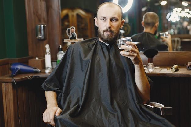 Mann sitzt auf einem stuhl. friseur mit einem kunden. guy trinkt einen whisky.