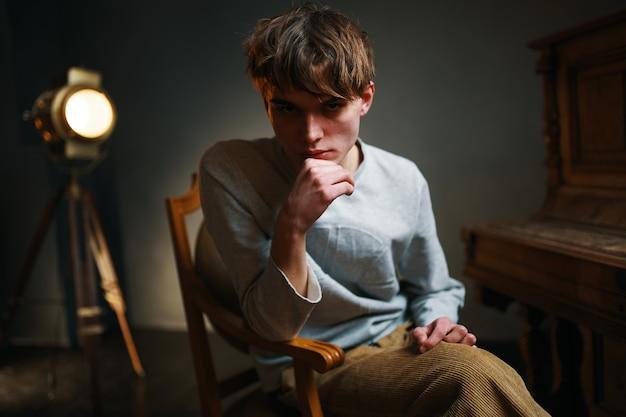 Mann sitzt auf einem stuhl neben dem klavier und posiert foto
