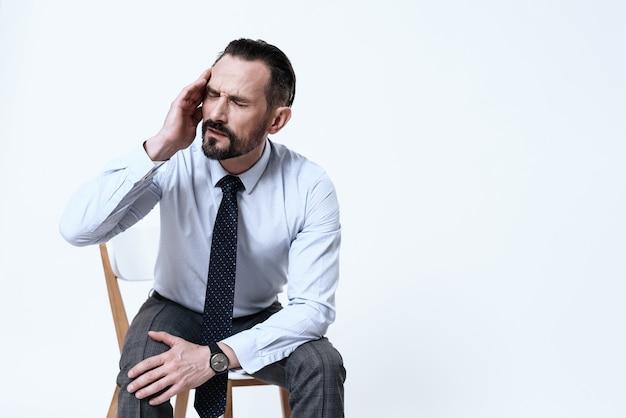 Mann sitzt auf einem stuhl und fasst seinen kopf.