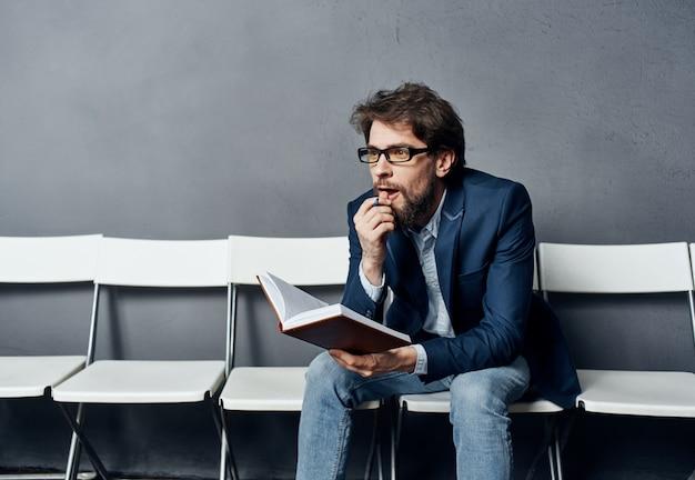 Mann sitzt auf einem stuhl und wartet auf jobinterview-arbeitslebensstil-emotionen