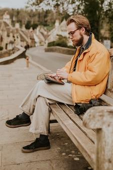 Mann sitzt auf einer bank und arbeitet an tablet im dorf