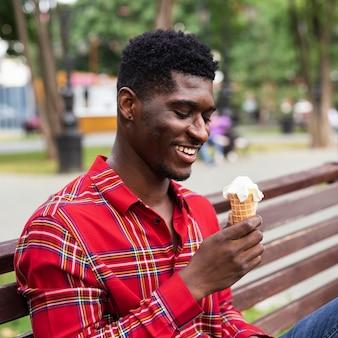 Mann sitzt auf einer bank und isst eis