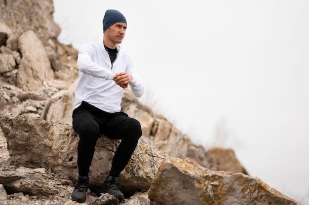 Mann sitzt auf felsen in der natur