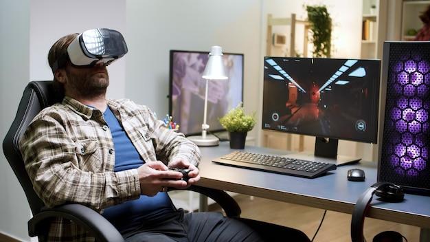 Mann sitzt auf gaming-stuhl und zieht sein vr-headset aus. spiel vorbei für männliche spieler mit langen haaren.