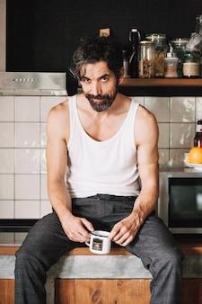 Mann sitzt auf küchentisch