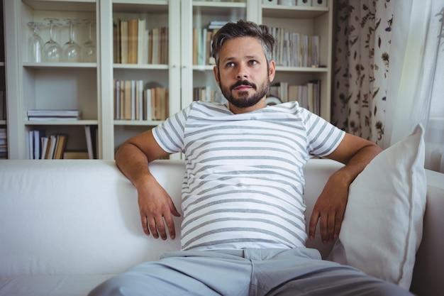 Mann sitzt auf sofa im wohnzimmer