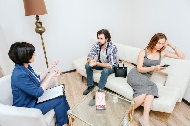 Mann sitzt auf sofa und betrachtet psychologen. er hört ihr sehr vorsichtig zu. junge frau lehnt sich zum rand des sofas und betrachtet telefon. sie kümmert sich nicht um therapie.