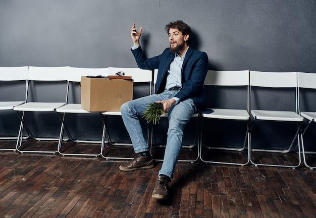 Mann sitzt auf stühlen mit einer box jobsuche