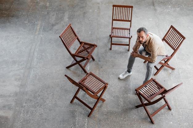 Mann sitzt auf stuhl voller schuss