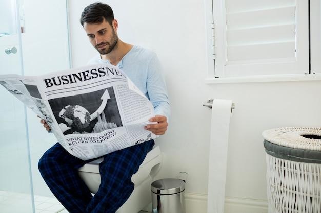 Mann sitzt auf toilettensitz und liest zu hause eine zeitung
