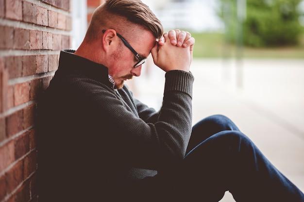 Mann sitzt beim beten in der nähe der wand