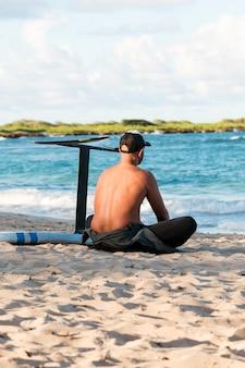 Mann sitzt draußen neben seinem surfbrett