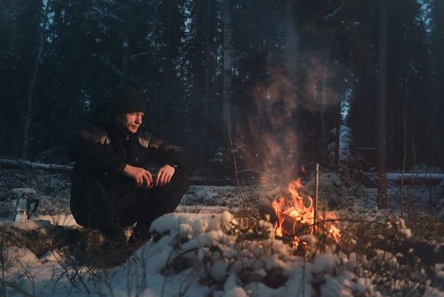 Mann sitzt im abendlichen winterwald in der nähe des feuers.