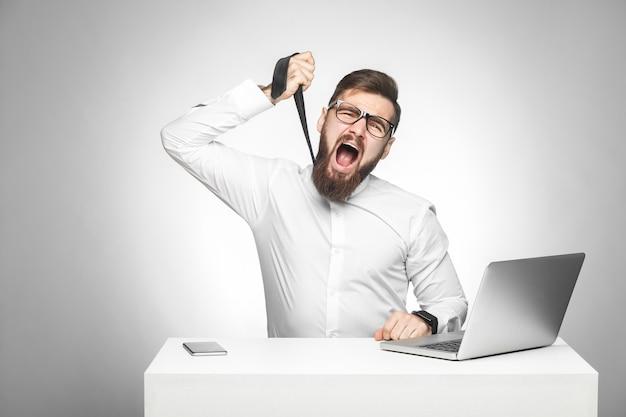 Mann sitzt im büro und versucht sich mit krawatte zu erwürgen