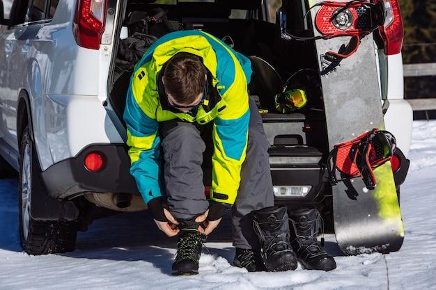 Mann sitzt im kofferraum des autos und wechselt für snowboard.close up