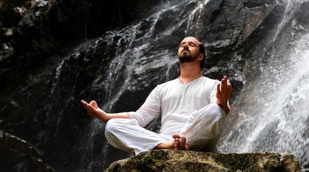 Mann sitzt im meditationsyoga auf felsen am wasserfall