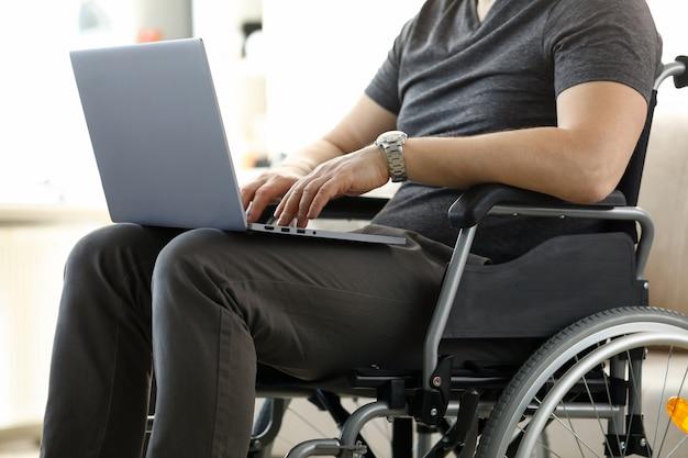 Mann sitzt im rollstuhl, der mit laptop-computer arbeitet