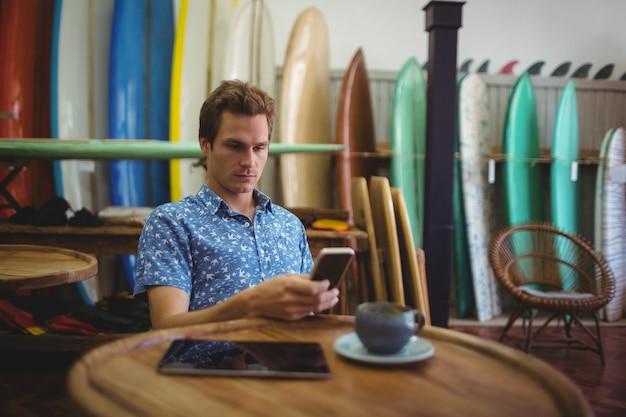 Mann sitzt im surfbrettladen