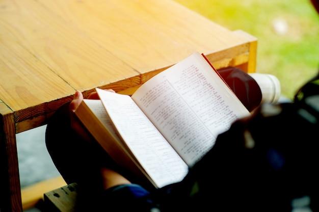 Mann sitzt im vintage-stuhl vor seinem haus an einem ruhetag lesen sie ein buch und entspannen sie sich. unscharfer hintergrund. horizontaler filmeffekt. das konzept des lesens von büchern zur verbesserung der selbsterkenntnis.