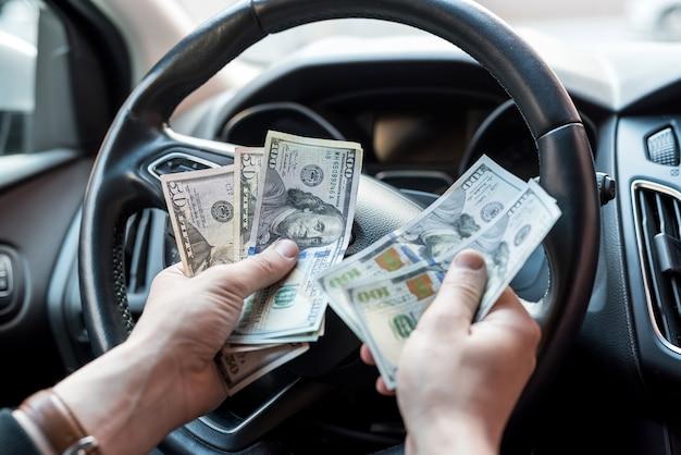 Mann sitzt in einem auto, das dollarbanknoten als bestechungsversicherung zählt