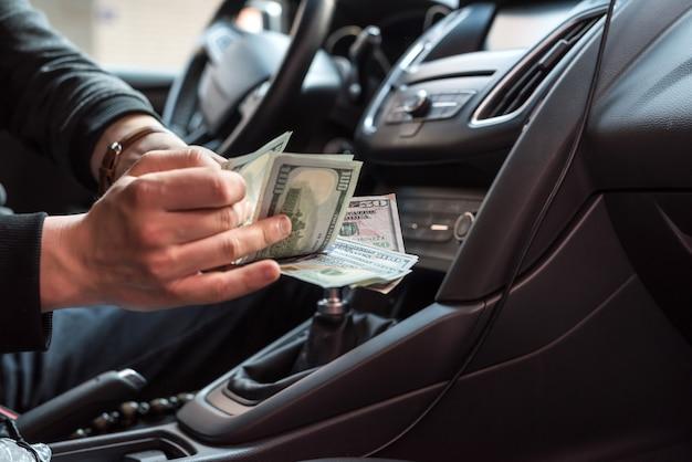 Mann sitzt in einem auto und zählt dollarbanknoten als bestechungsgelder
