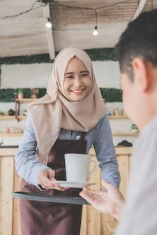 Mann sitzt in einem café, das mit kaffee gedient wird