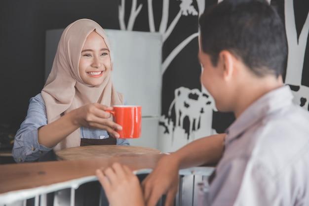 Mann sitzt in einer café-bar, die mit kaffee gedient wird