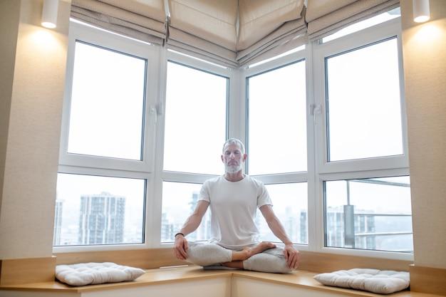 Mann sitzt in yoga-pose zu hause